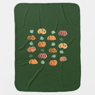 Calabazas con la manta del bebé de las hojas