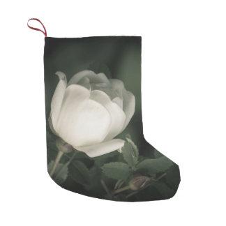 Calcetín Navideño Pequeño Dogrose blanco en un fondo oscuro. Añada su nombre