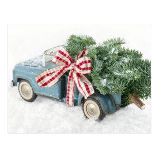 Camión azul del juguete que lleva un árbol de postal