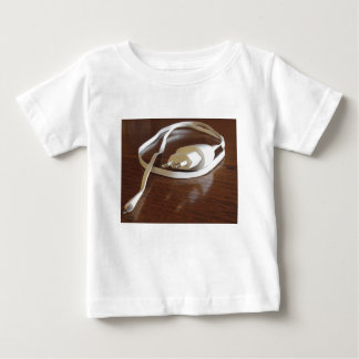 Camiseta De Bebé Cargador blanco del smartphone en la tabla de
