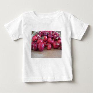 Camiseta De Bebé Cerezas maduras rojas en la bandeja de madera
