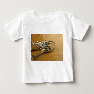 Camiseta De Bebé Manojo de llaves gastadas de la casa en la tabla
