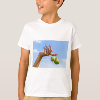 Camiseta Dé sostener dos peras verdes colgantes en cielo