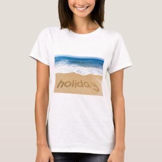 Camiseta Día de fiesta de la palabra escrito en arena en la