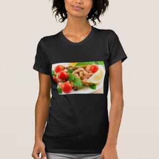 Camiseta Ensalada de pedazos blanqueados de mariscos en una