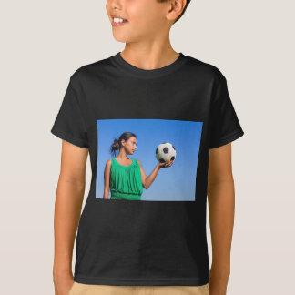 Camiseta Mujer joven que lleva a cabo fútbol en la mano con