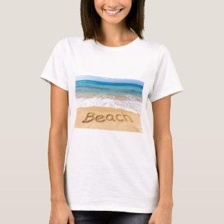 Camiseta Redacte la playa escrita en arena en el mar griego