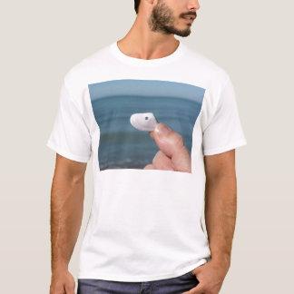 Camiseta Sostener un seashell en la mano con el mar azul