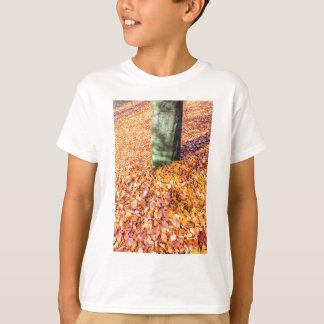 Camiseta Tierra alrededor del tronco de árbol cubierto con