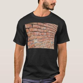 Camiseta Vista de una pared de ladrillo vieja con una falta