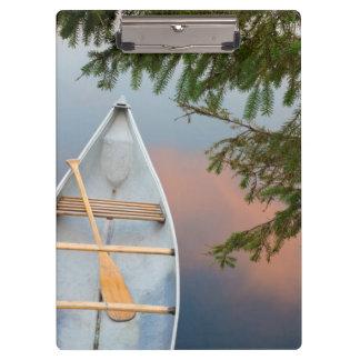 Canoa en el lago en la puesta del sol, Canadá