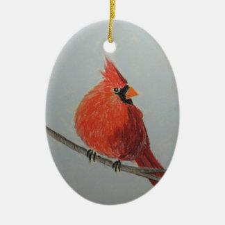 Cardenal rojo en rama en el ornamento de los adorno navideño ovalado de cerámica
