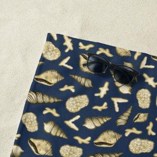 Cáscaras y coral de oro en la toalla de playa de
