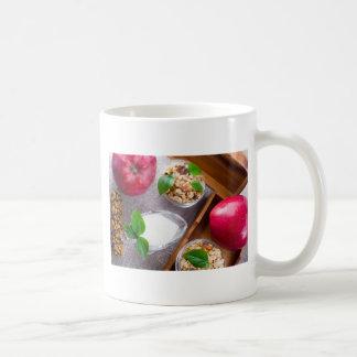 Cereal con las nueces y pasas, yogur y manzanas taza de café