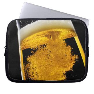 Cerveza vertido en el vidrio fundas portátiles