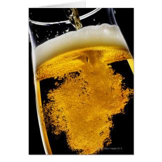 Cerveza vertido en el vidrio tarjeta de felicitación