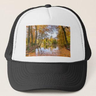 Charca del bosque cubierta con las hojas en la gorra de camionero
