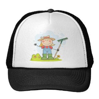 Chica del granjero con un rastrillo en hierba gorras