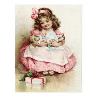 Chica del vintage en vestido rosado con la muñeca postal
