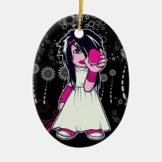 chica lindo del emo que lleva a cabo arte del adorno navideño ovalado de cerámica