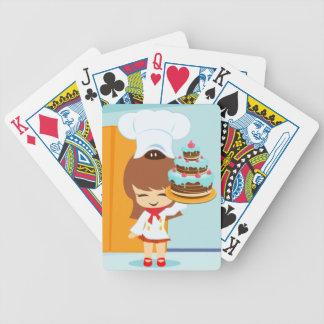Chica lindo que sostiene la torta de cumpleaños de baraja de cartas