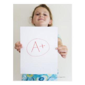 Chica que muestra apagado A+ grado en el papel Postal