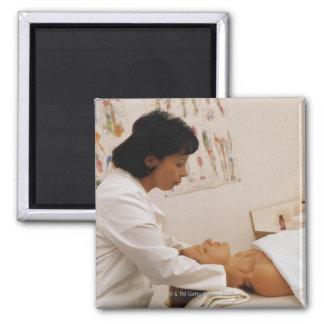 Chiropractor de sexo femenino que da masajes a un  imanes de nevera