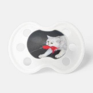 Chupete Gato blanco que juega tirando del juguete rojo