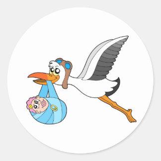 Cigüeña del vuelo que entrega al bebé pegatina redonda