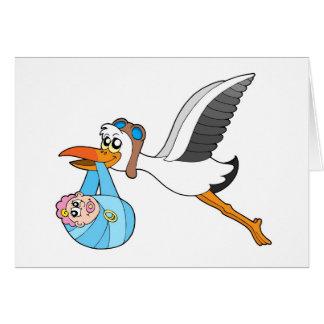 Cigüeña del vuelo que entrega al bebé tarjeta de felicitación