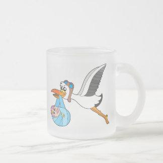 Cigüeña del vuelo que entrega al bebé taza de cristal