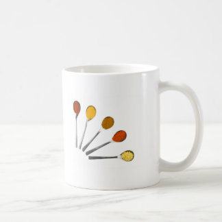 Cinco especias de aderezo en las cucharas del taza de café