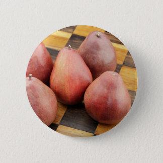 Cinco peras rojas en un tablero de ajedrez de chapa redonda de 5 cm