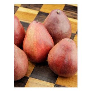 Cinco peras rojas en un tablero de ajedrez de postal