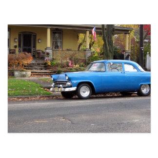 Coche azul en postal de la pequeña ciudad