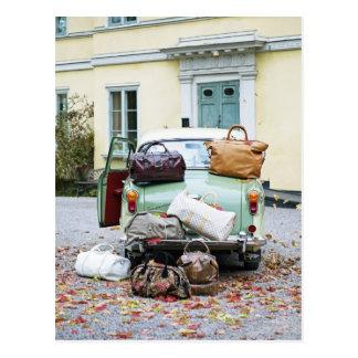 Coche del vintage con las porciones de equipaje tarjeta postal