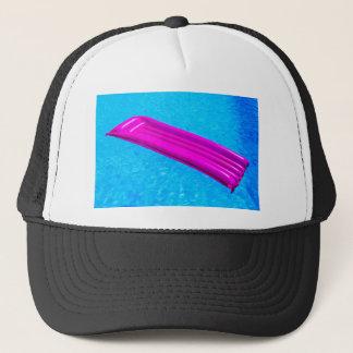 Colchón de aire rosado en el agua de la piscina gorra de camionero