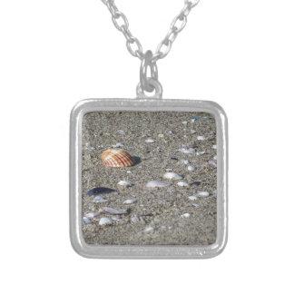 Collar Plateado Seashells en la arena. Fondo de la playa del