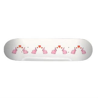 Conejos rosados lindos con los corazones rojos del monopatin