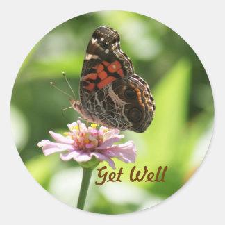 Consiga bien, la mariposa, zinnia en una etiqueta