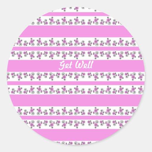 Consiga bien, las flores minúsculas, rosadas en un etiquetas redondas