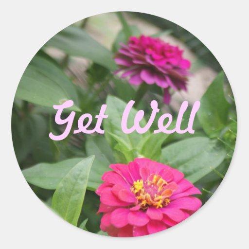 Consiga bien, las flores minúsculas, rosadas en un etiqueta redonda