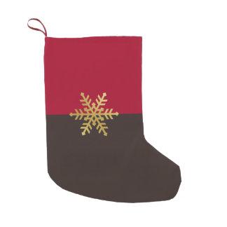 Copos de nieve del oro en el almacenamiento del calcetín navideño pequeño