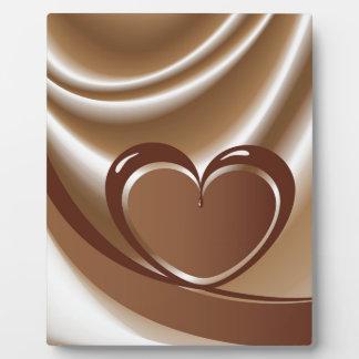 Corazón del chocolate de una cinta en el fondo de placa expositora