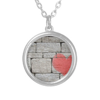 Corazón rojo de la pintada en la pared de piedra collar plateado