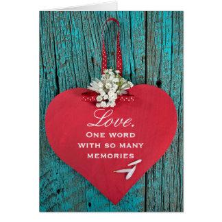 corazón rojo de madera del aniversario con el ramo tarjeta de felicitación