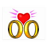 Corazón sobre los anillos de bodas postales