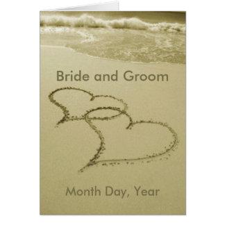 Corazones en la invitación del boda de la arena