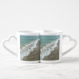 Corazones que entrelazan románticos en la playa set de tazas de café