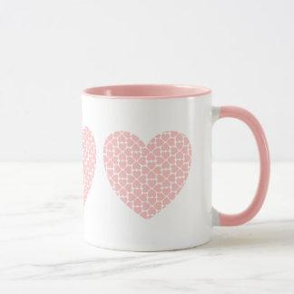 Corazones rosados dentro de la taza del trío de